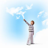 Cute boy catching clouds Stock Photos