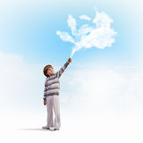 Cute boy catching clouds. Image of little cute boy catching clouds in sky Royalty Free Stock Photo