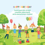 Cute boy celebrating birthday with her friends in the park. Group of happy children congratulates his friend on his birthday. Cute boy blowing on candles on Stock Photos