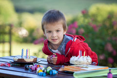 Cute boy, celebrating his fifth birthday outdoor. With a cake and presents Stock Photography
