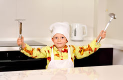 Cute boy chef displaying his utensils Royalty Free Stock Image
