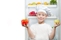 Cute boy Chef near the open refrigerator Royalty Free Stock Images