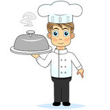 Cute boy chef presenting a meal Royalty Free Stock Photography