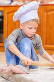 Cute boy in chef`s hats sitting on the kitchen floor soiled with flour, playing with food, making mess and having fun Royalty Free Stock Photography