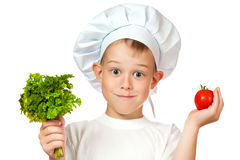 Cute boy Chef is smiling. raw vegetables Stock Photos