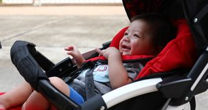 Cute boy child in baby stroller carriage seat stock footage