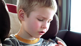 Cute boy in a child car seat plays with a toy Royalty Free Stock Images