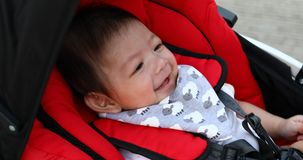 Cute boy child in baby stroller carriage seat stock video