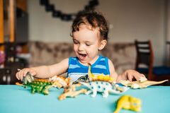 Cute boy child playing at home with toy dinosaurs at the table
