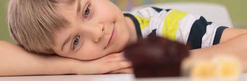 Cute boy and chocolate cupcake Stock Photos