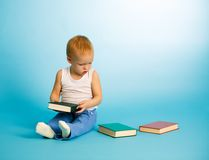 Cute boy chooses what to read from three books. Two years old cute boy chooses what to read from three books. Over blue background Stock Photography