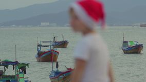 Cute boy in the Christmas cap sits on the railing and looking at fishing boas in sea. Asia. Vietnam. Christmas. New Year stock video