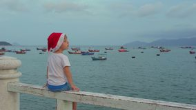 Cute boy in the Christmas cap sits on the railing and looking at fishing boas in sea. Asia. Vietnam. Christmas. New Year stock footage
