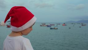 Cute boy in the Christmas cap sits on the railing and looking at fishing boas in sea. Asia. Vietnam. Christmas. New Year stock video footage