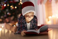 Cute boy in Christmas hat reading book at home royalty free stock photography
