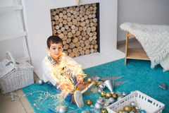 Cute boy with a christmas lights sits on a floor. A Cute boy with a christmas lights sits on a floor Royalty Free Stock Image