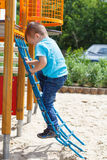 Cute boy climbing at playground Stock Photos