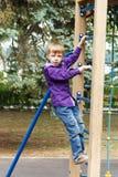 Cute boy climbing a rope ladder Royalty Free Stock Photo