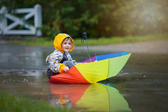 Cute boy with colorful rainbow umbrella on a rainy day, having f Royalty Free Stock Image