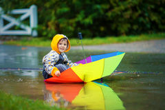 Cute boy with colorful rainbow umbrella on a rainy day, having f Royalty Free Stock Photo