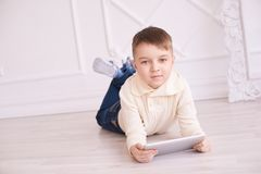 Cute boy. Computer tablet. Training. light interior. Cute beautiful boy. Computer tablet. Training. light interior. White background Stock Photography