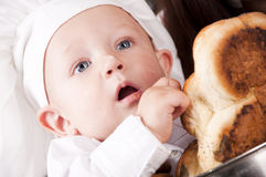 Cute boy in a cook pan. Portrait of a baby wearing a chef hat sitting inside a large cook pan Stock Photo