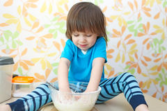 Cute boy cooks at home kitchen Royalty Free Stock Photography