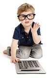 Cute boy counting with calculator. Cute boy wearing bit glasses doing maths with fingers and calculator Stock Photography