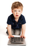 Cute boy counting with calculator. Cute boy doing maths with big calculator Royalty Free Stock Photography