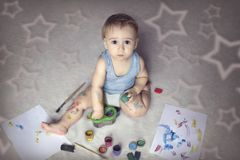 Cute boy covered in paint sitting on the floor among the items for creativity. And looking at the camera stock photos