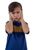 Cute boy covering his ears against white background Royalty Free Stock Images