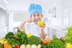 Cute boy cutting lemon in kitchen Royalty Free Stock Images