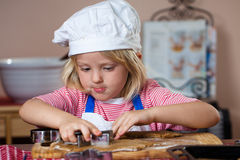 Cute boy cutting out gingerbread shapes Royalty Free Stock Photos