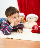 Cute boy daydreaming lying on the floor. New Year Royalty Free Stock Image