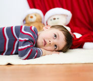 Cute boy daydreaming lying on the floor. New Year Royalty Free Stock Photos