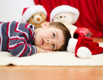 Cute boy daydreaming lying on the floor. New Year Stock Image