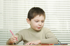 Cute boy at desk with crayons Royalty Free Stock Photos