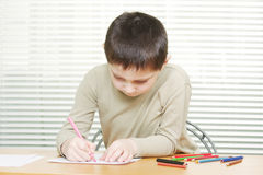 Cute boy at desk drawing with crayons Stock Photo