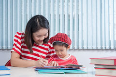 Cute boy doing his school homework with his mother, at home, he. Asian cute boy doing his school homework with his mother, at home, he is writing on a book stock image