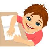 Cute boy doing homework top view Stock Photos