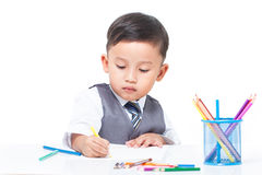 Cute boy drawing with colorful crayons Royalty Free Stock Images