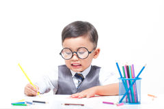 Cute boy drawing with colorful crayons Royalty Free Stock Photos