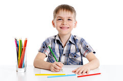 Cute boy drawing with colourful pencils Royalty Free Stock Image