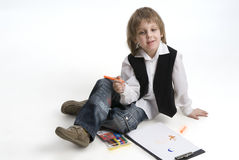 Cute boy drawing with crayons Stock Image