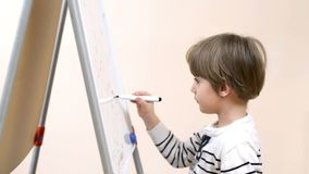 Cute Boy Drawing. At kindergarten on a white board stock video