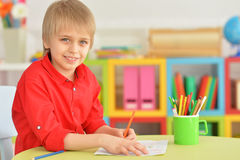 Cute boy drawing with pencils Stock Images