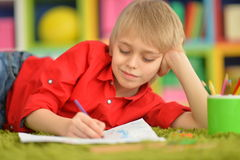 Cute boy drawing with pencils Royalty Free Stock Images