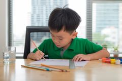 Cute boy is drawing using color pencils, isolated over white stock photography
