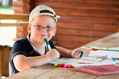 Cute boy drawing in wooden gazebo Stock Image