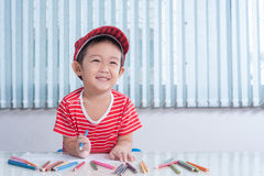 Cute boy draws with color pencils in the children's room Royalty Free Stock Photo